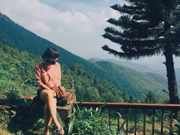Cô gái ngồi tại khuôn viên Belverder Tam Đảo nhìn xuống view sườn núi