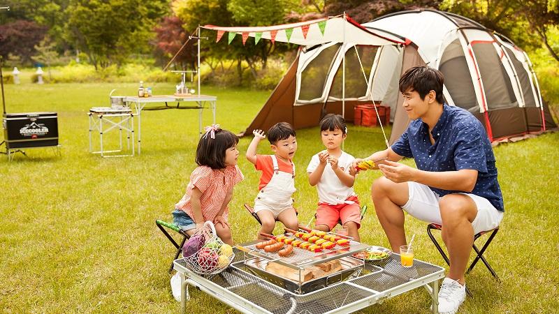 3 bé nhỏ và 1 người đàn ông đang nướng đồ ăn khi đi cắm trại