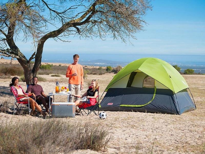 4 người đang trò chuyện vui vẻ và cắm trại ở trên đồi