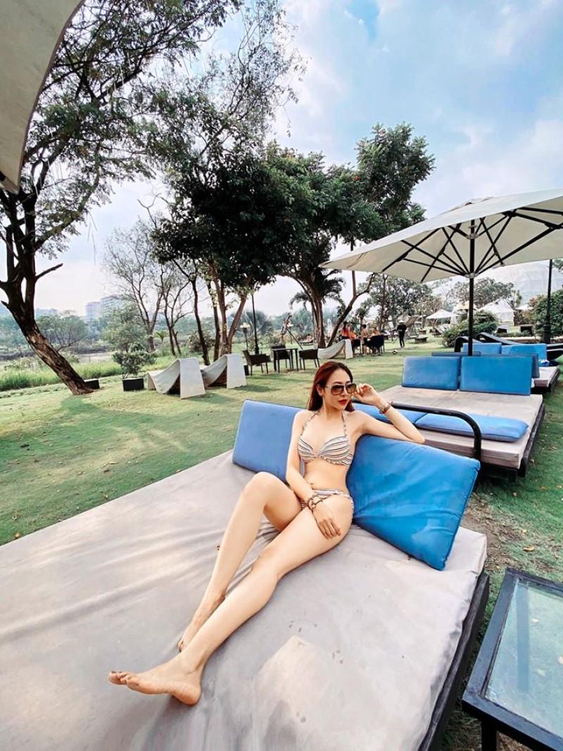 Cô gái mặc bikini chụp ảnh trên ghế nghỉ dưỡng bên hồ bơi