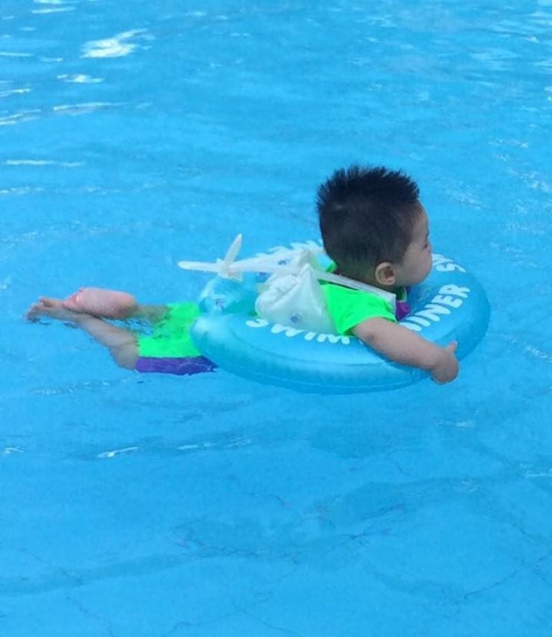 Em bé mặc phao bơi tập bơi trong hồ nước