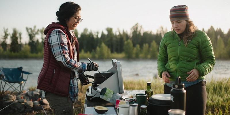 2 người đang chế biến đồ ăn khi đi dã ngoại