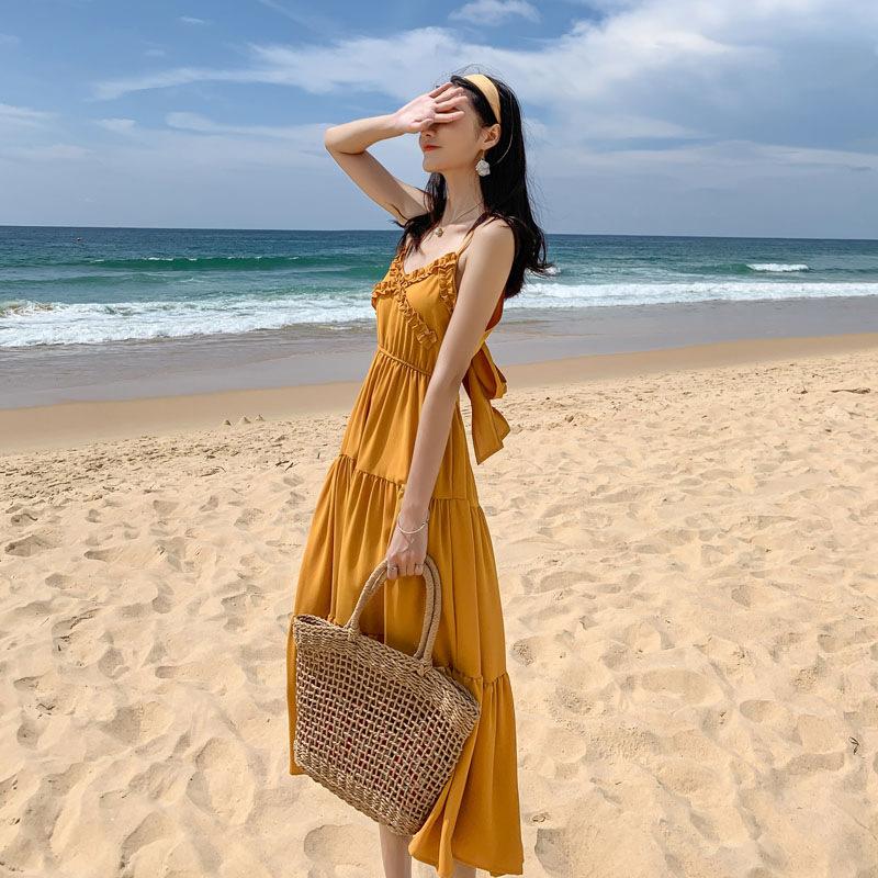 Cô gái nữ tính với băng đô và váy maxi tầng và túi cói