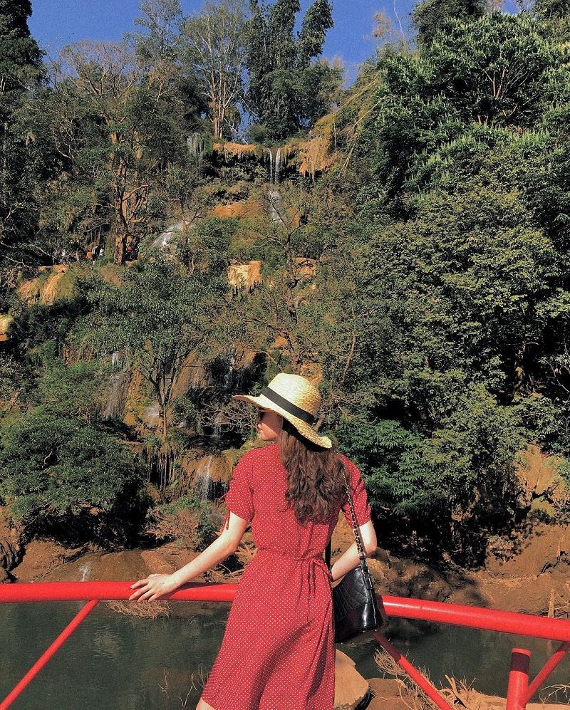 cô gái mặc váy đỏ đứng trên cầu bên thác Dải Yếm