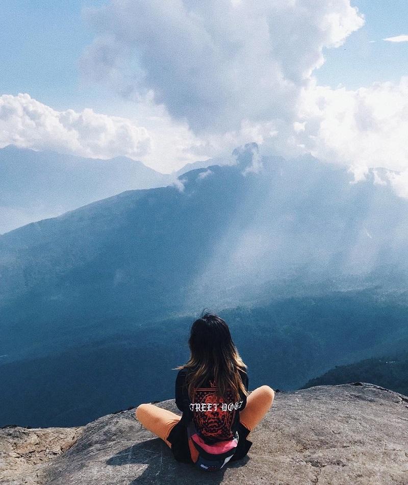 Cô gái ngồi trên mỏm núi đá