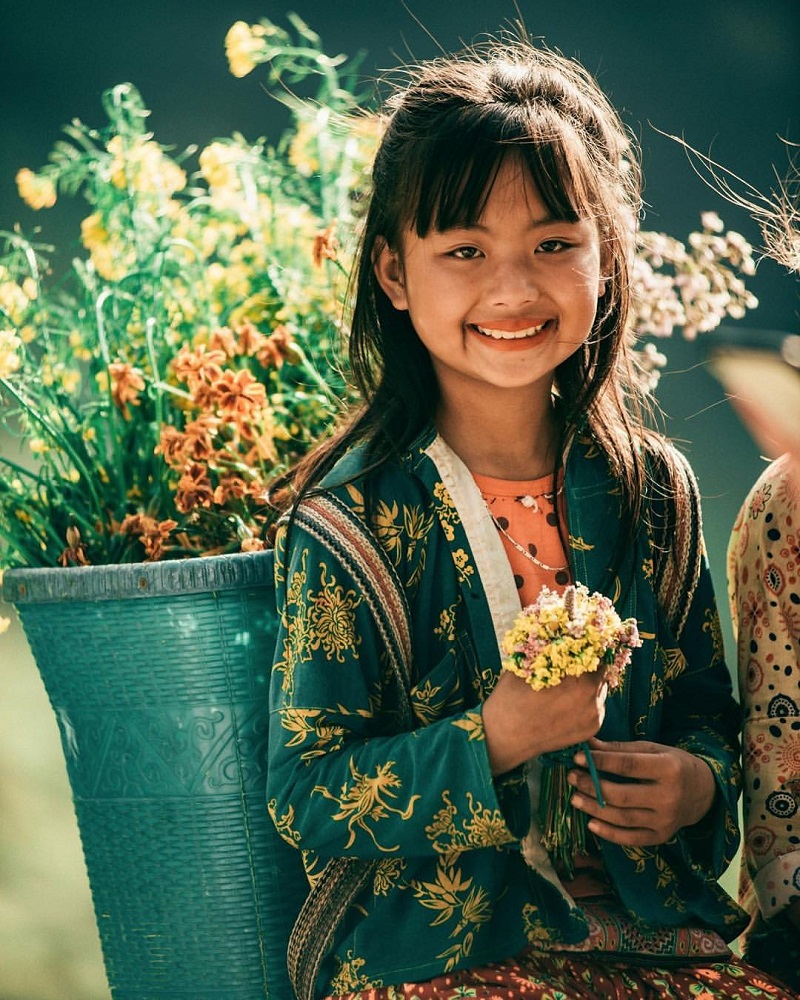 Em bé dân tộc đeo gùi hoa