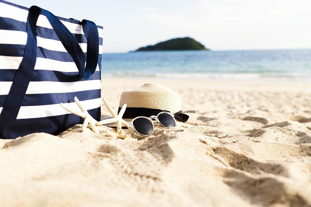 Túi xách, mũ cói, kính râm đi biển, cát trắng và 2 con sao biển