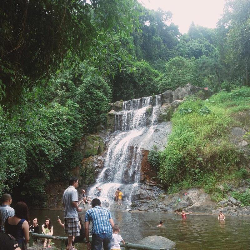 Nhiều người đang vui chơi trong hồ nước và dòng thác ở Ao Vua Ba Vì