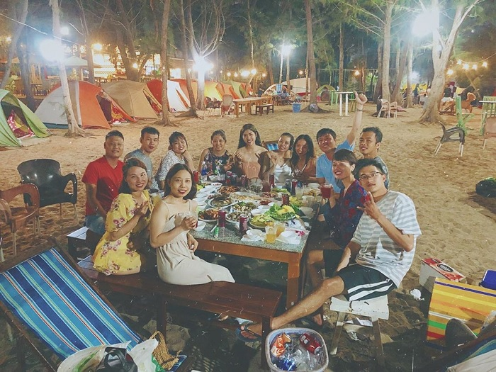 Nhóm bạn tổ chức ăn uống tại điểm cắm trại vào buổi tối