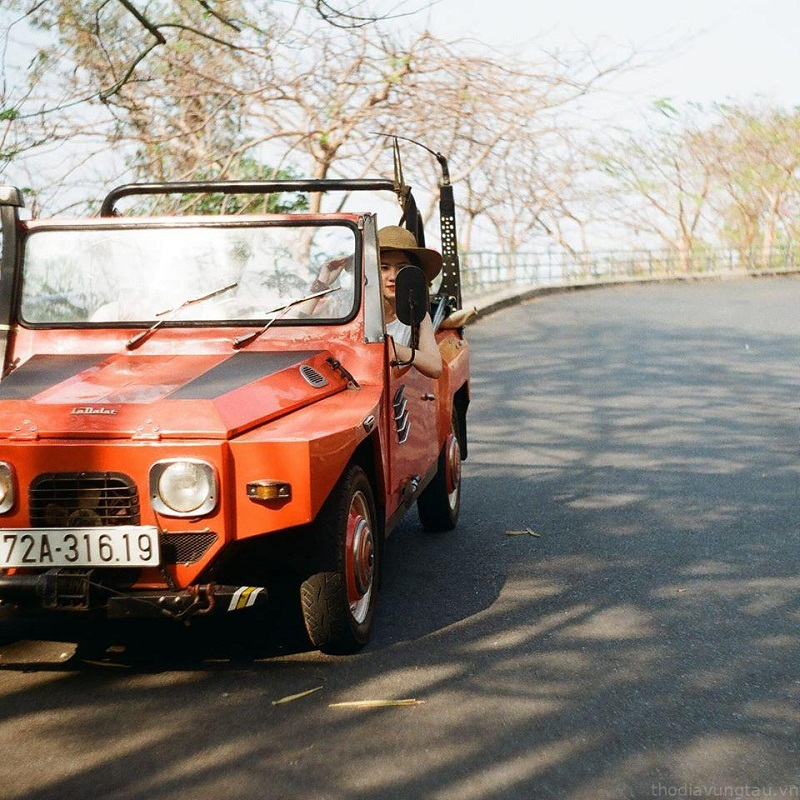 Cô gái trên chiếc xe jeep màu đỏ trên một con đường thơ mộng