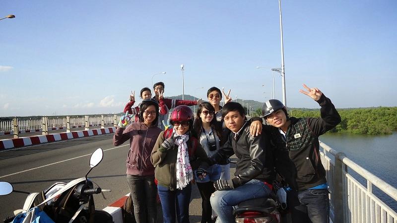 Nhiều bạn trẻ đi xe máy dừng chân chụp hình bên cây cầu