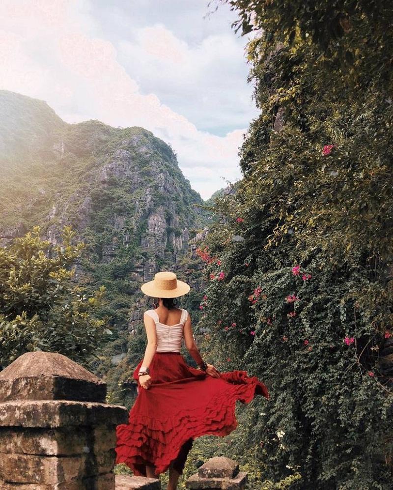 Cô gái mặc váy đỏ di chuyển tại đoạn đường lên Hang Múa