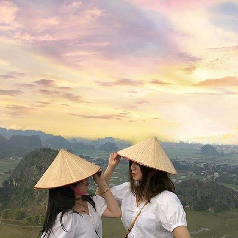 2 bạn gái đội nón giữa khung cảnh Hang Múa