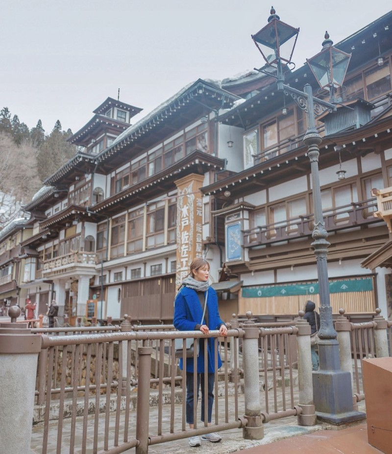 Cô gái đứng trên cầu tại thị trấn Ginzan