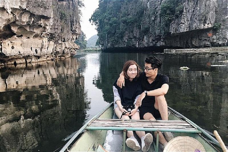 1 bạn nam và 1 bạn nữ ngồi trên thuyền khám phá các hang động