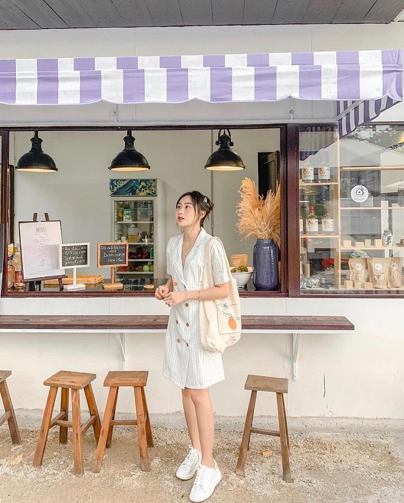 Một cô nàng măc set đồ váy cổ bẻ trắng với túi tote cực kỳ hợp khi chụp ảnh ở quán cà phê Đà Lat.