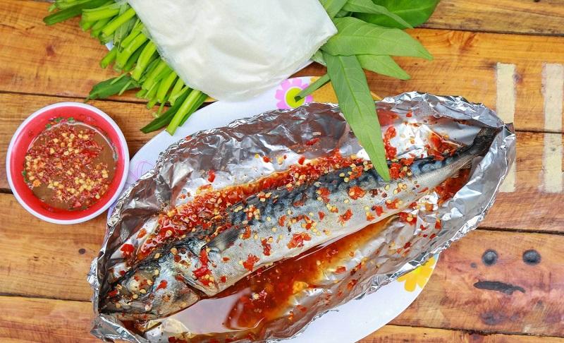 Cá nục nướng muối ớt được bọc kèm giấy bạc trên đĩa và nước chấm