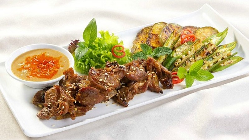 Thịt dê nướng bày trí cùng với các loại rau ăn kèm và nước chấm