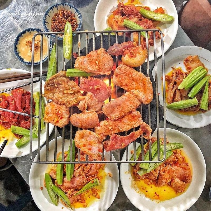 Thịt nướng trên vỉ nướng than hoa ăn kèm với đậu bắp và các món khác