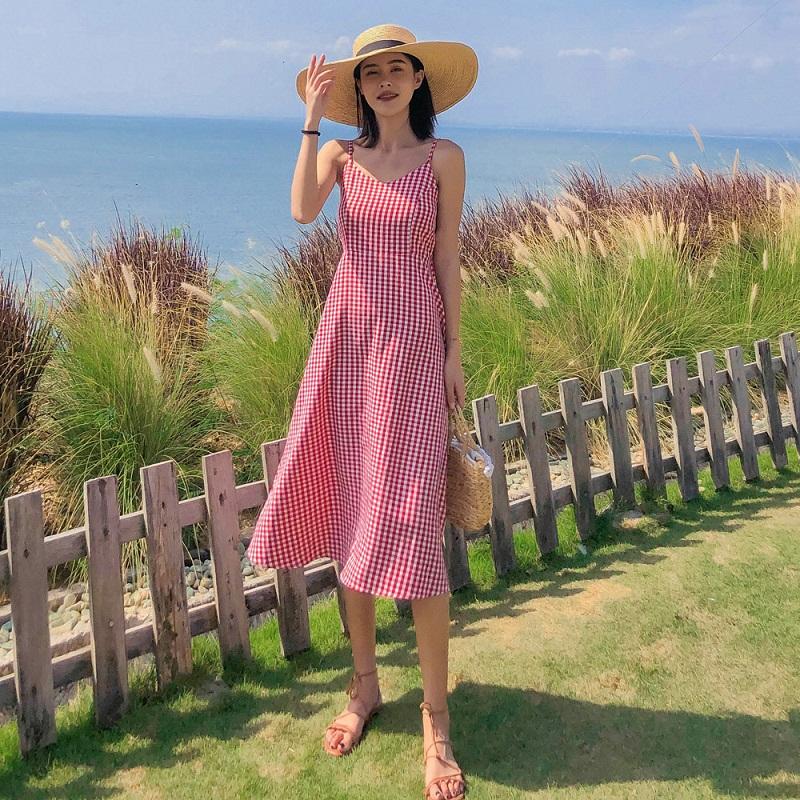Váy kẻ caro kết hợp với các phụ kiện đi biển như mũ cói, túi cói và dép sandal