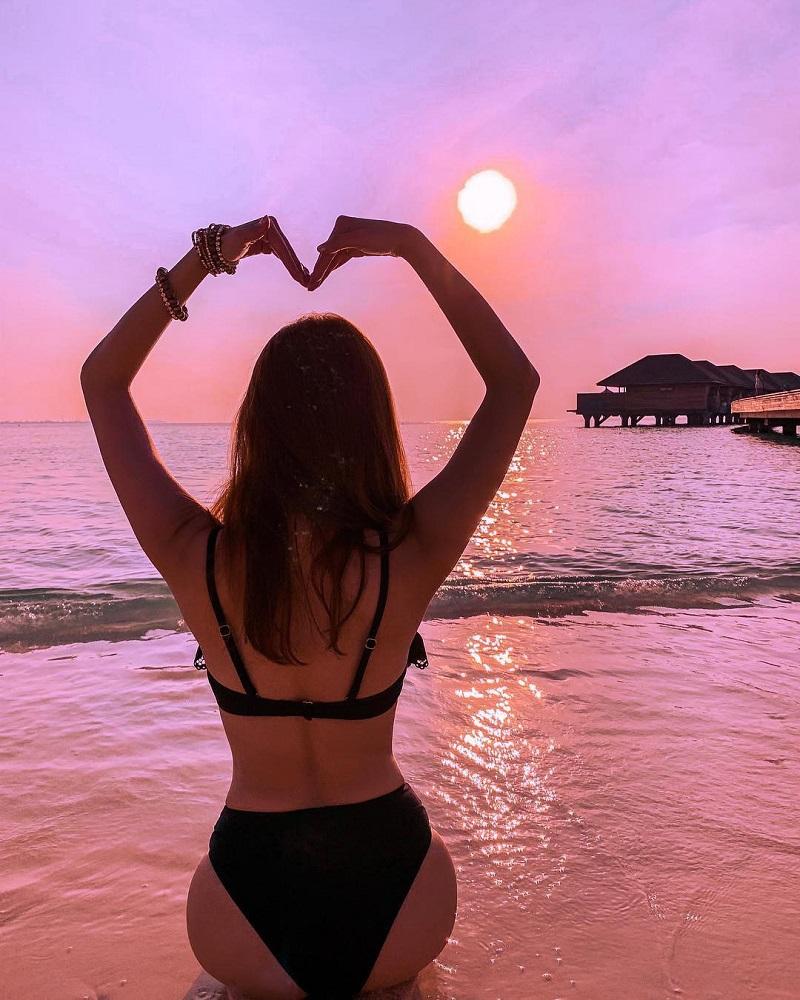 Cô gái tạo dáng hình trái tim trên bờ biển