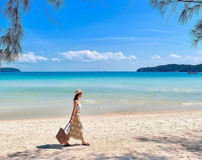 Cô gái đang bước đi trên bờ biển cát trắng