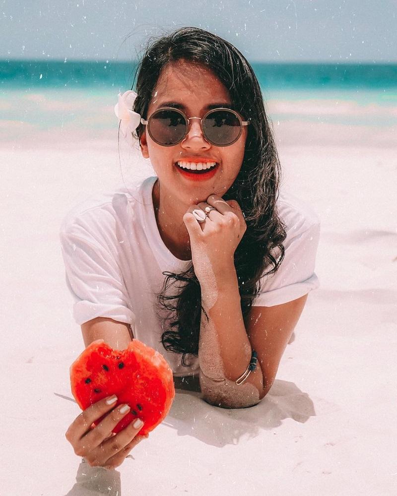 Cô gái có mái tóc cài hoa đang nở 1 nụ cười thật tươi trước ống kính