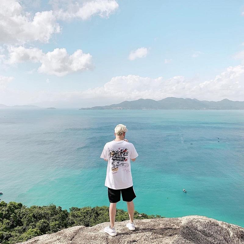 1 bạn nam đứng trên mỏm đá hướng về khung cảnh biển trong lành xanh mát