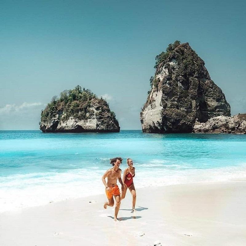 2 người 1 nam 1 nữ đang vui chơi trên bãi biển trong lành