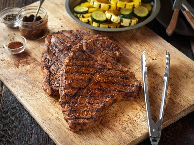 Thịt bò nướng nguyên tảng bày trên thớt với kẹp gắp và các gia vị chế biến