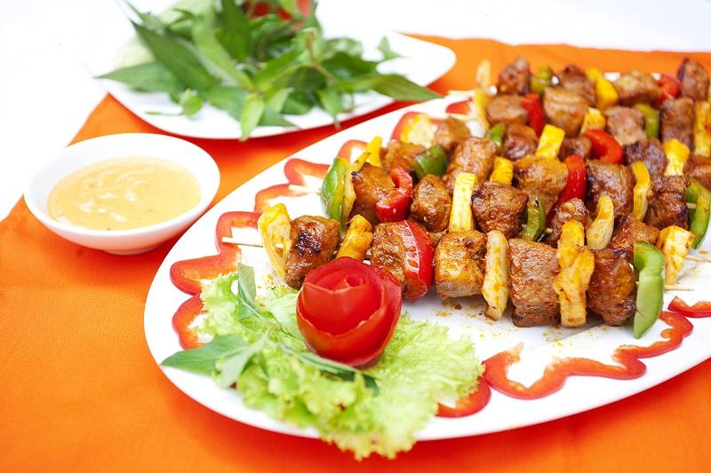 Những xiên bò nướng cùng với các loại rau củ bày trí trên đĩa