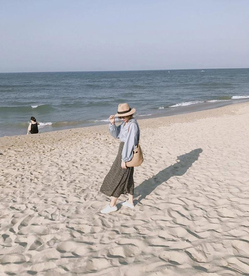 Một cô nàng mặc chân vày dài chụp ảnh thướt tha trên bãi cát Hải Tiến