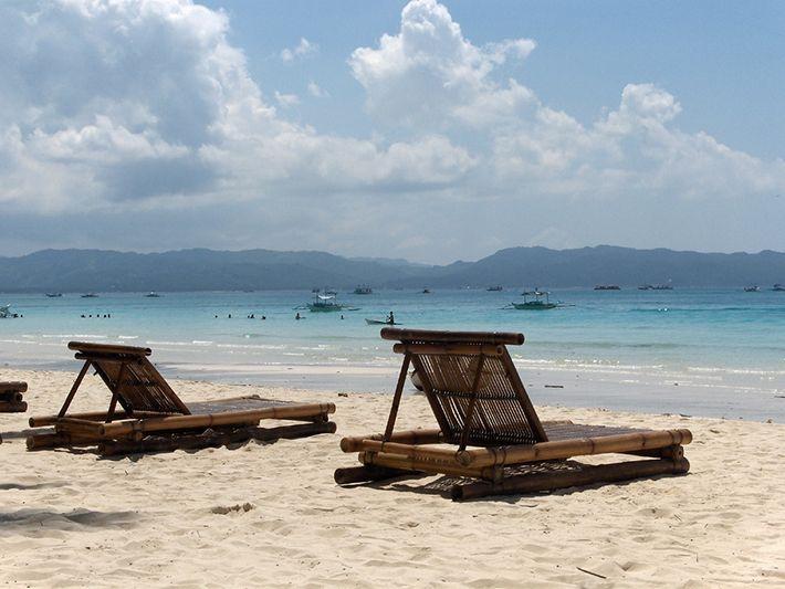 Những chiếc ghế xếp bằng gỗ đặt trên bãi cát nhìn ra biển xanh