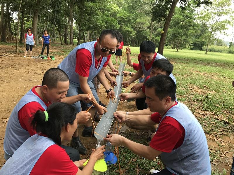 Một nhóm đang giữ các máng nước để hoàn thành trò góp gạo thổi cơm chung
