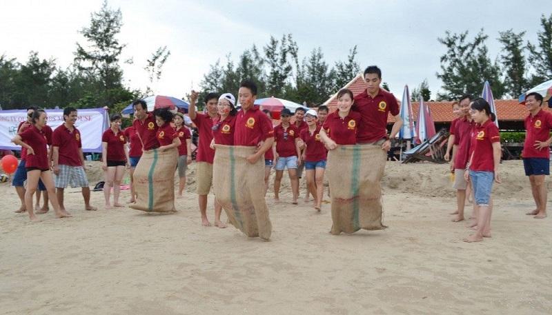 Team áo đỏ chơi trò nhảy bao bố trên bãi cát
