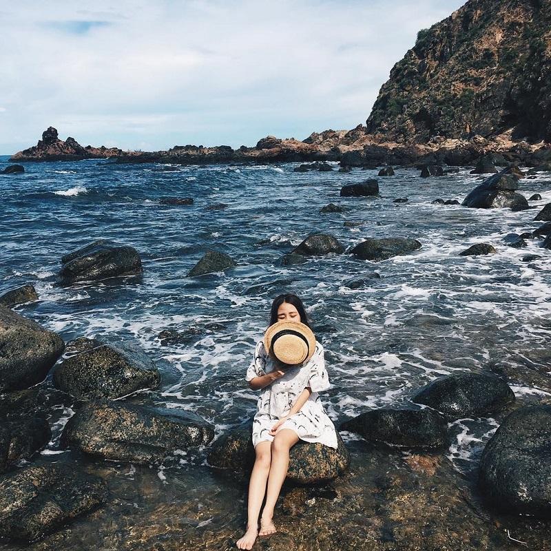 Cô gái ngồi trên những mỏm đá ở biển