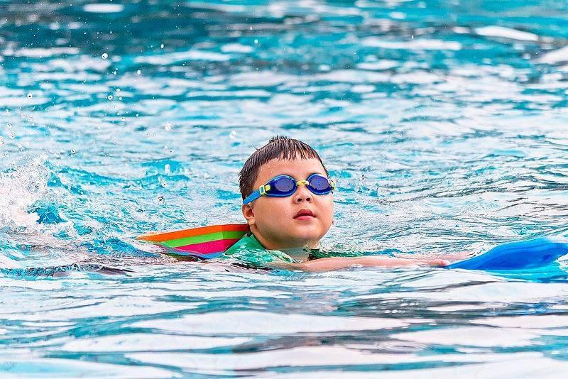 Một cậu bé mặc đồ bơi đang bơi lội trong làn nước xanh mát