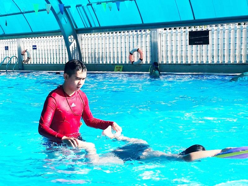 Huấn luyện viên đang dạy bơi cho em nhỏ