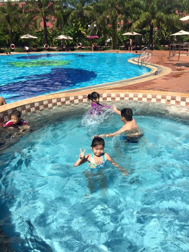 Các em nhỏ đang bơi lội vui đùa trong hồ bơi