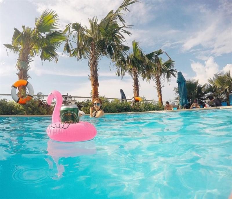 Cô gái chụp ảnh ở hồ bơi nước xanh ngắt