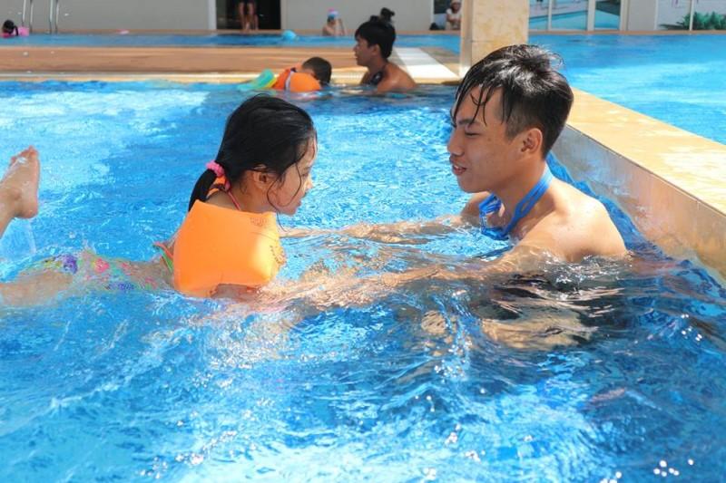 HLV đang dạy em nhỏ tập bơi trong hồ