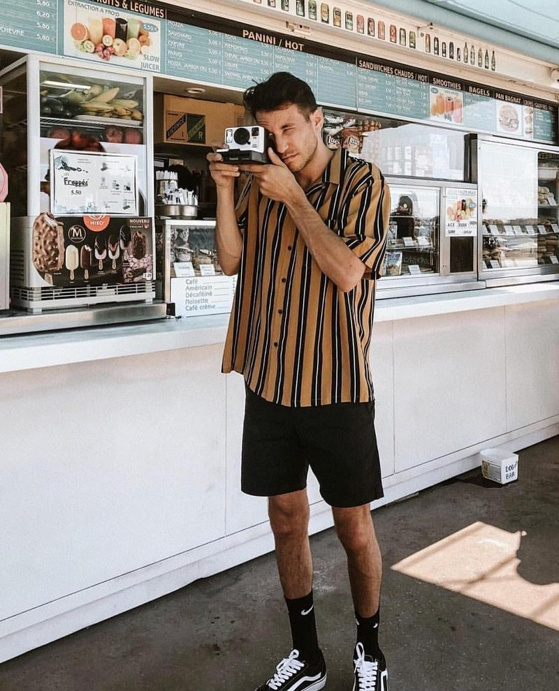 chàng trai sử dụng máy ảnh đang mặc một chiếc quần short đen và áo sơ mi kẻ