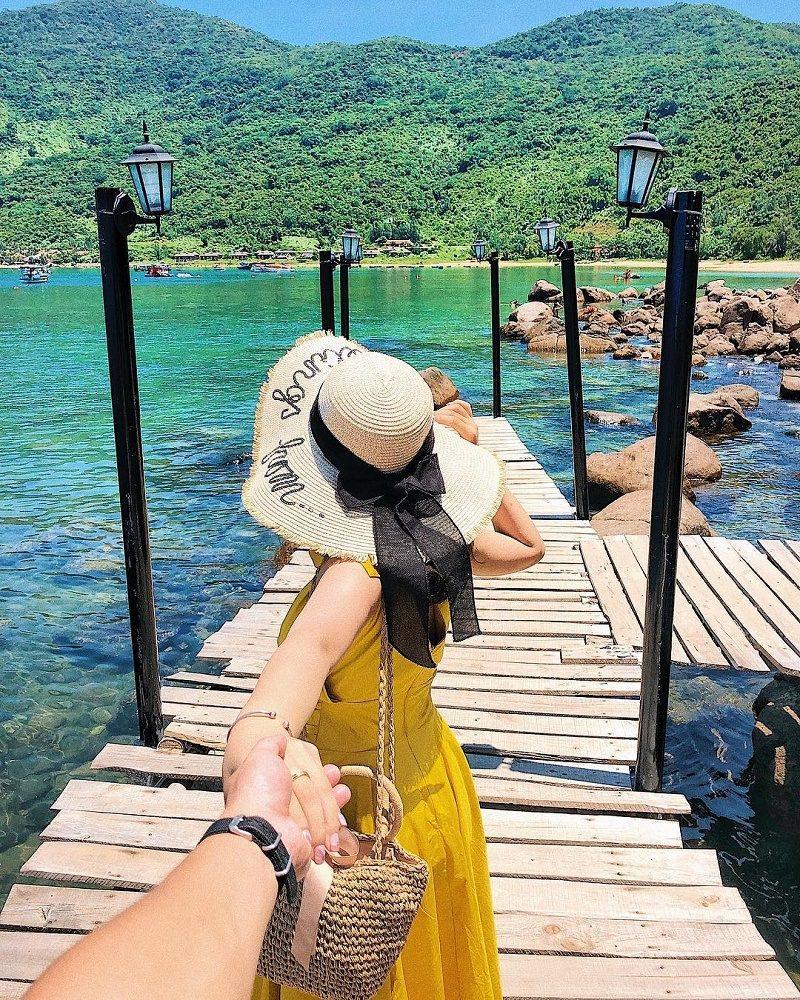 cô gái mặc váy vàng đội mũ vành rộng đứng trên cầu hướng ra đảo