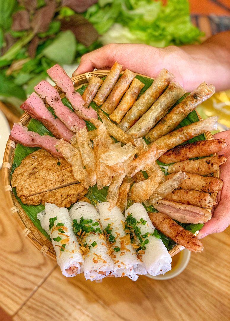 Một mẹt đầy ắp các loại nem nướng khác nhau cuốn cùng rau sống chấm nắm nêm.