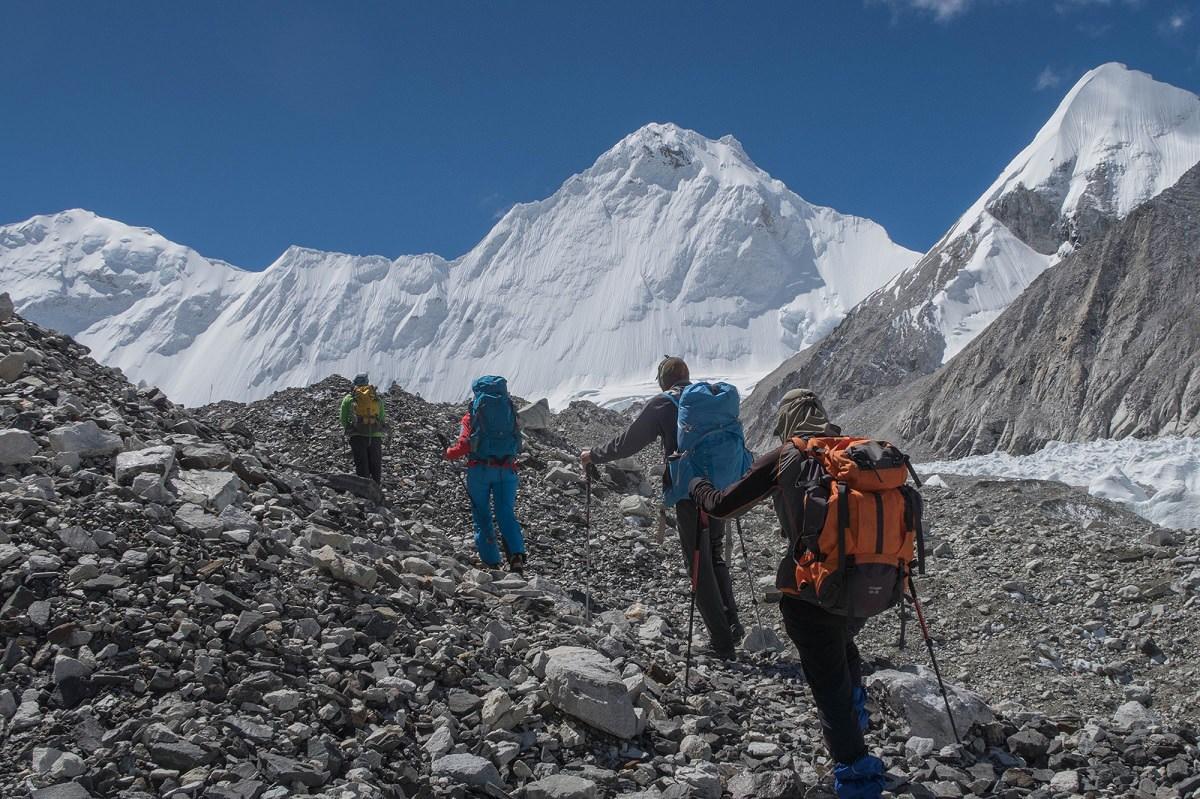 4 người trong đoàn leo núi di chuyển qua đoạn đường sỏi đá lên đỉnh Cho Oyu