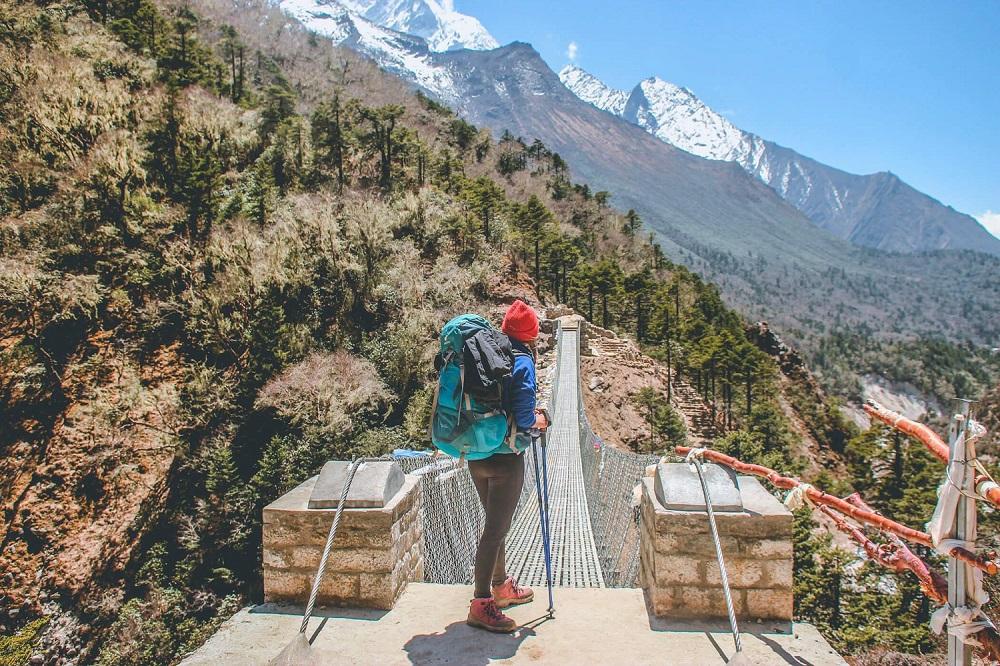 người phụ nữ đội mũ đỏ đeo balo đang chuẩn bị bước qua cây cầu kẽm gai