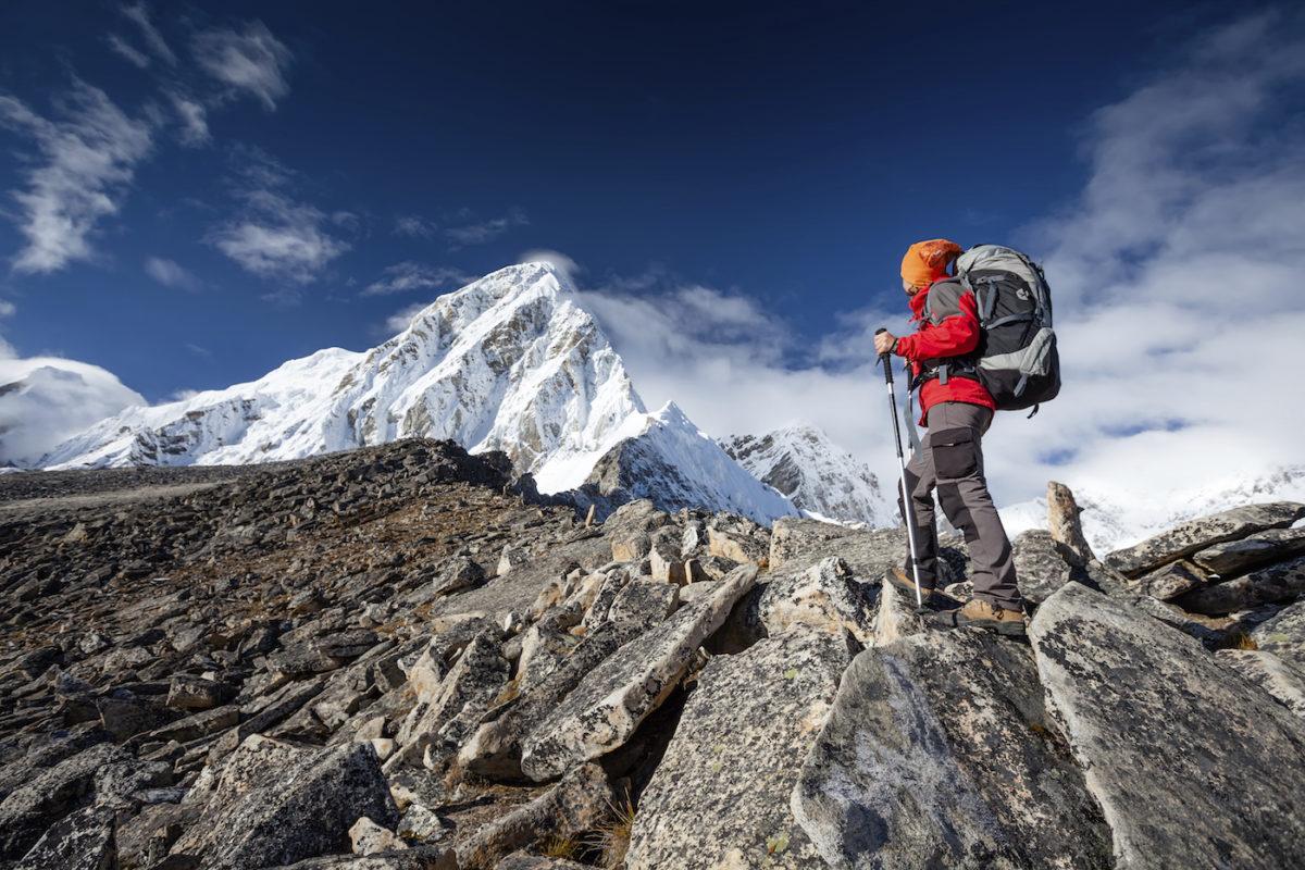 người đàn ông mặc áo đỏ cầm gậy leo núi chinh phục núi đá