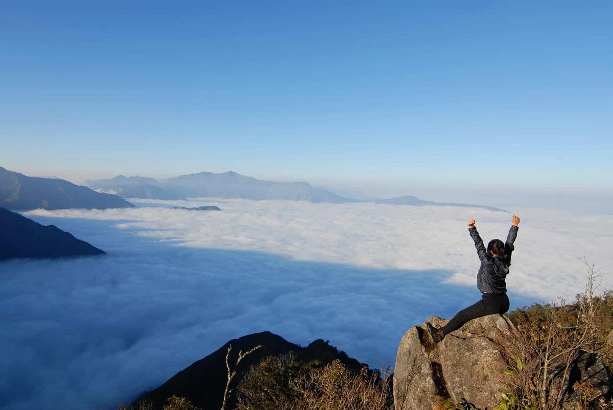 cô gái ngồi trên đỉnh núi giữa mây ngàn và bầu trời xanh ngát