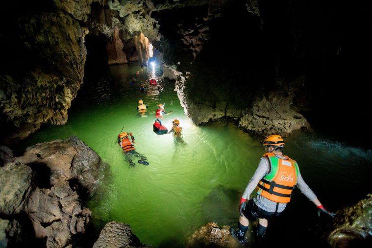 Cả đoàn thám hiểm mặc áo phao bơi qua sông ngầm ở hang Hung Ton.