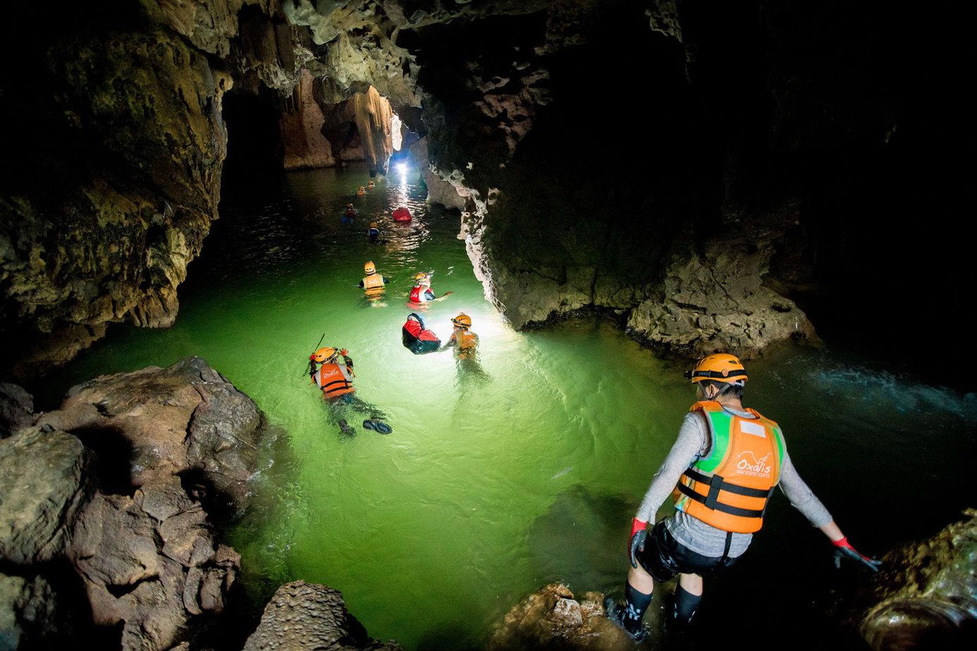 Cả đoàn thám hiểm mặc áo phao đang bơi qua sông ngầm ở hang Hung Ton.